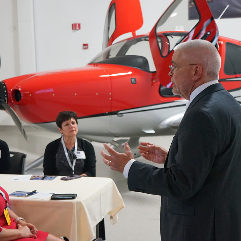 a man talking to an audience with an airplane in the background